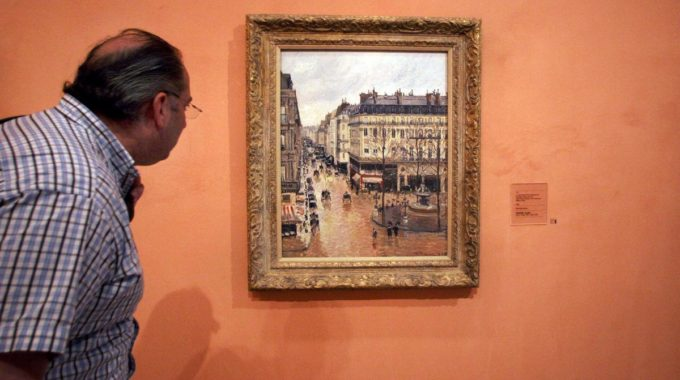 "CORRECTS CAPTION THROUGHOUT TO REFLECT LATEST DEVELOPMENTS ON STORY - FILE- In This May 12, 2005 File Photo An Unidentified Visitor Looks At The Impressionist Painting Called ""Rue St.-Honore, Apres-Midi, Effet De Pluie"" Painted In 1897 By Camille Pissarro, On Display In The Thyssen-Bornemisza Museum In Madrid.  A Federal Judge In California Has Dealt A Blow To A Jewish Family's Prolonged Battle To Regain Ownership Of The Masterpiece Seized From A Woman Fleeing Nazi Germany In 1939 And Now On Display In The Museum In Spain. Judge John Walter Found That Under Spanish Law, The Thyssen-Bornemisza Museum In Madrid Is The Rightful Owner Of ""Rue Saint-Honore, Apres-midi, Effet De Pluie."" In Last Week's Ruling, Walter Dismissed A 2005 Lawsuit Filed By The Woman's Heirs Against The Museum, But Urged The Institution To Consider What Would Be Fair To Victims Of Nazi Persecution. (AP Photo/ Mariana Eliano, File)"