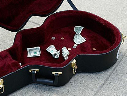 Open busker guitar case with donated bills and coins