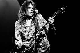 A Youthful Neil Young With His Guitar
